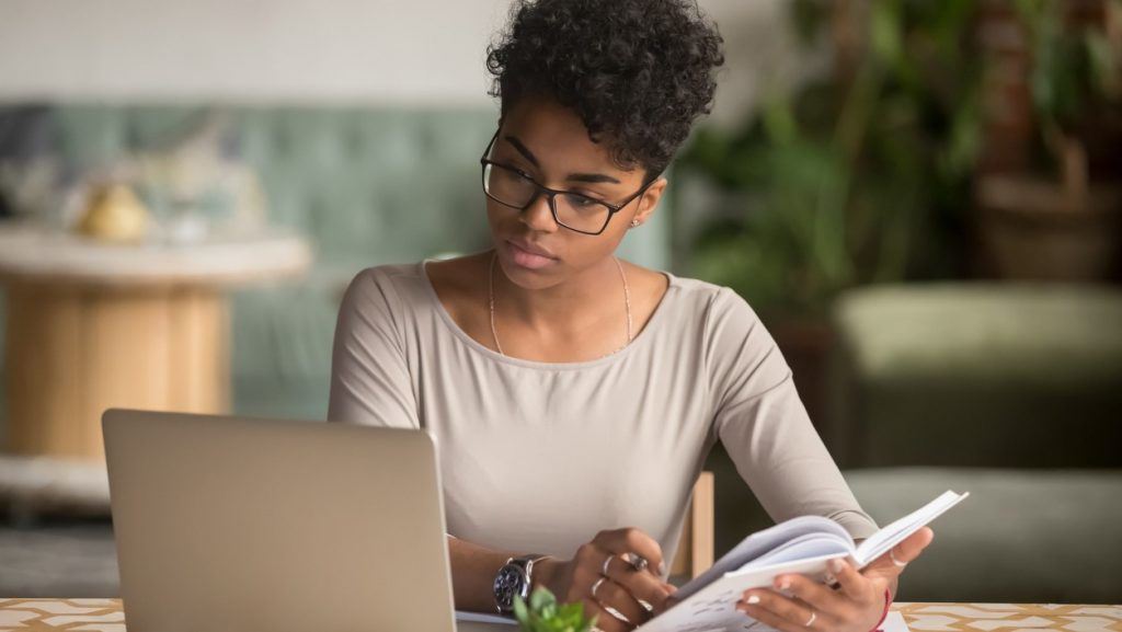 Focused young african american businesswoman or student looking at laptop holding book learning, serious black woman working or studying with computer doing research or preparing for exam online. concept: credit factoring