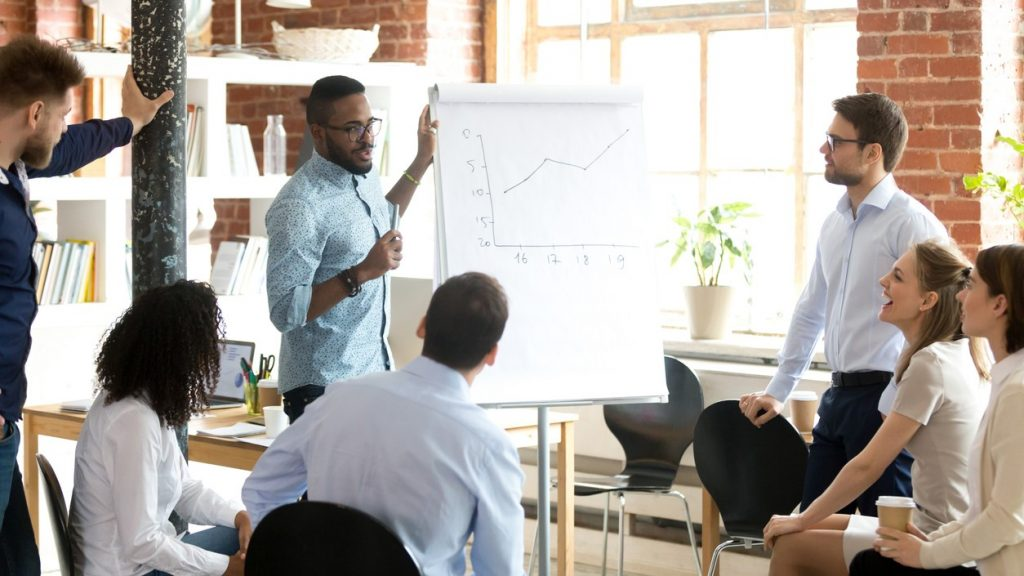 Confident smiling African American business coach speaking presentation to colleagues group at briefing, company meeting, explaining growth of sales graph, reporting about good result, motivating workers. concept: digital marketing mistakes