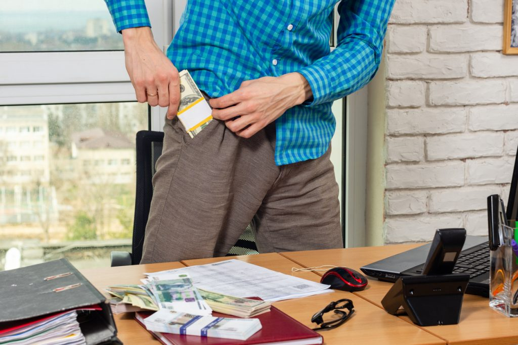 Office worker puts a wad of money in his pocket. Concept: How to prevent fraud.