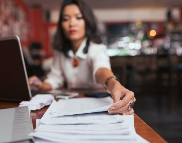 Business lady working with financial documents on her desk. Concept: tax tips