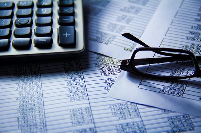 Facturas, lentes y calculadora. Concepto: Cómo aumentar el flujo de caja de tu empresa.