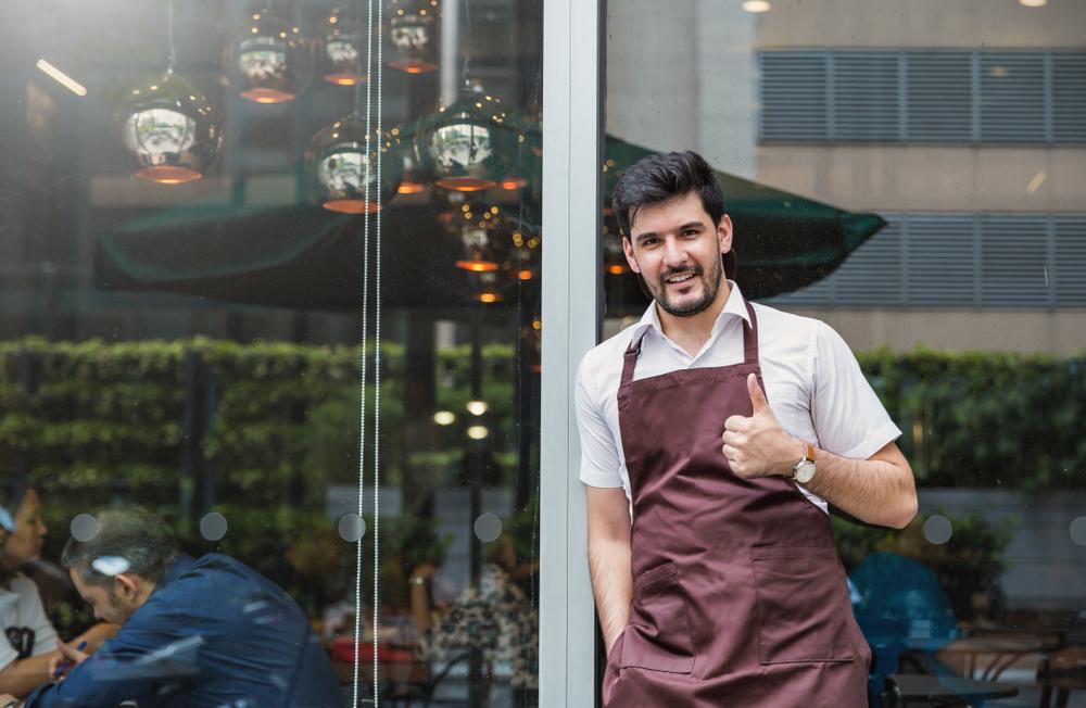"""Dueño latino de una pequeña empresa a la puerta del negocio y mostrando pulgar hacia arriba para ilustrar la idea """"pequeña empresa exitosa"""""""