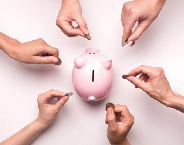 Togetherness concept. People hands throwing coins in piggy bank , white background. concept: loan stacking