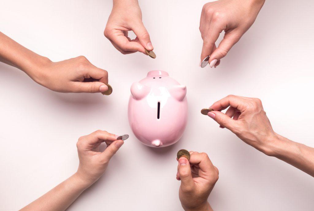 muchas personas poniendo monedas en una alcancía. concept: acumulación de préstamos