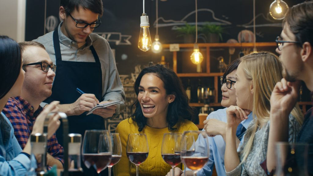 In the Bar/ Restaurant Waiter Takes Order From a Diverse Group of Friends. Beautiful People Drink Wine and Have Good Time in this Stylish Place. concept: online marketing