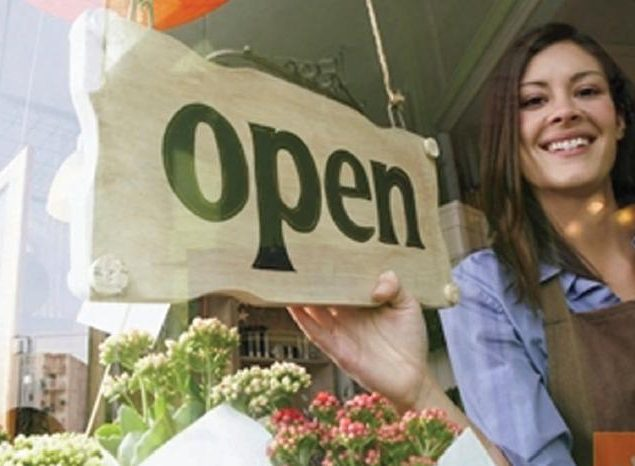 Woman placing open sign in business door. Concept: the cost of starting a business