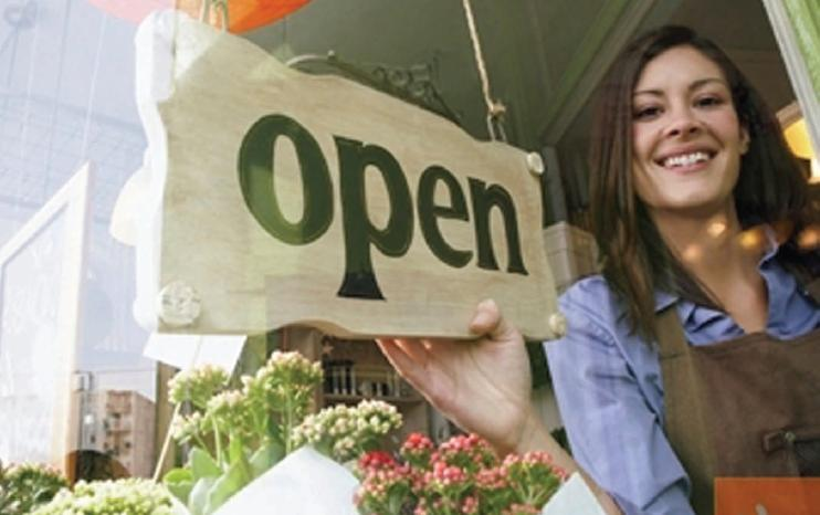 Woman placing open sign in business door. Concept: tHow much does it cost to start a business