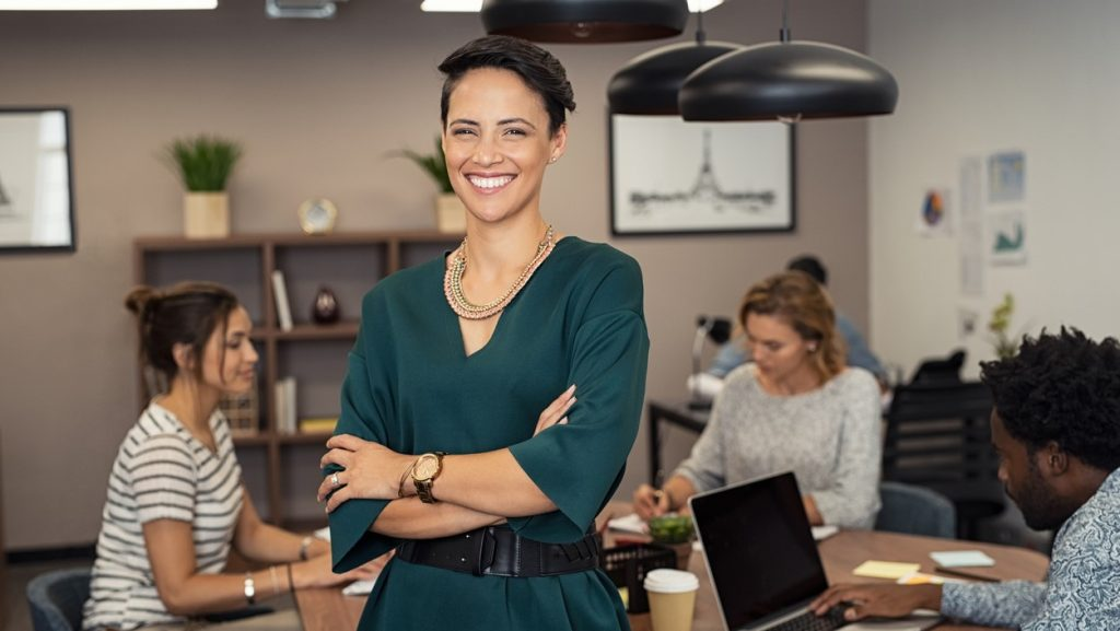 Portrait of successful business woman standing with her colleagues working in background at office. Portrait of cheerful fashion girl in green dress standing with folded arms and looking at camera. Beautiful businesswoman feeling proud and smiling. concept: cost to start a business