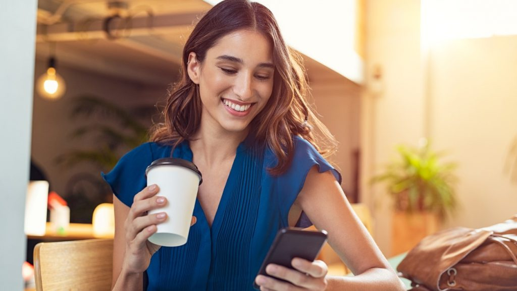 Young beautiful woman holding coffee paper cup and looking at smartphone while sitting at cafeteria. Happy university student using mobile phone. Businesswoman in casual clothes drinking coffee, smiling and using smartphone indoor. concept: yelp profile