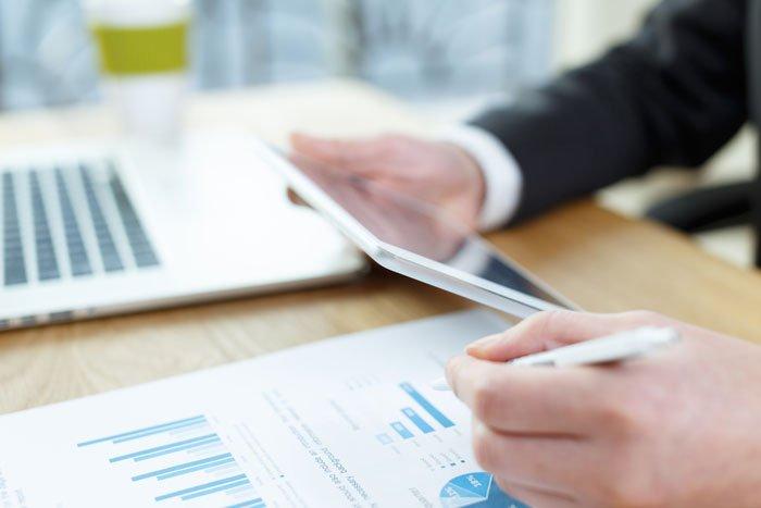 """Manos sobre tableta y papeles de presupuesto para ilustrar la idea """"Cómo hacer un presupuesto"""""""