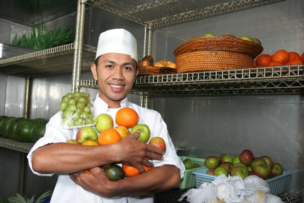 Chef sosteniendo frutas en almacén. Cocepto: fórmula del costo de alimentos