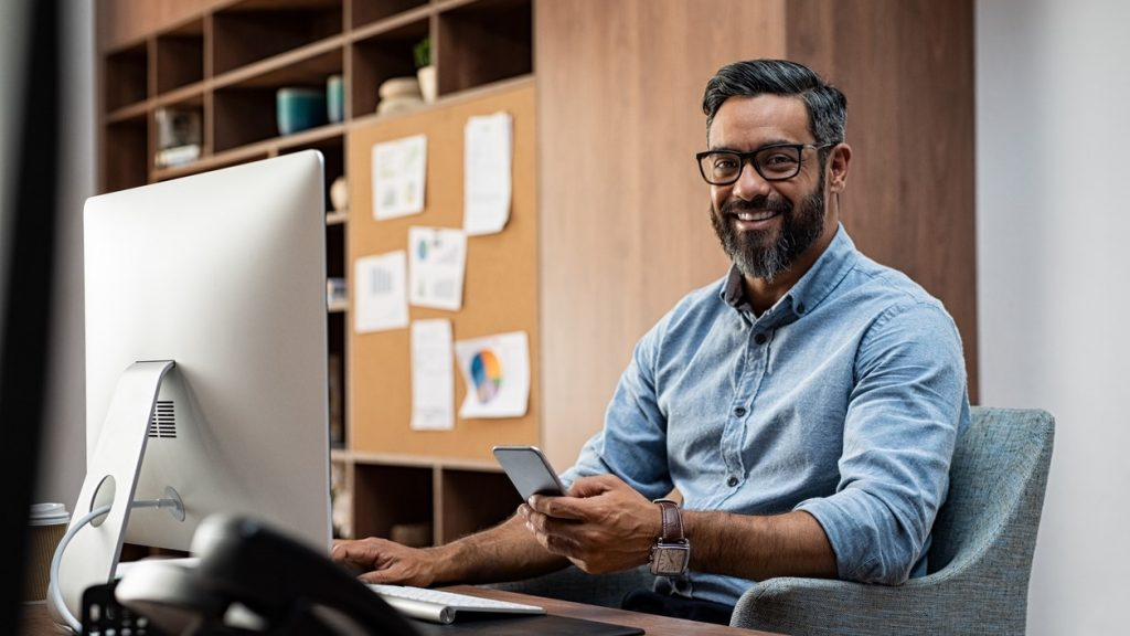 Smiling business man wearing eyeglasses working on desktop computer while using phone in office. Middle eastern businessman using smartphone while sitting at desk in office designer. Man working in modern business environment.. concept: strategic plan