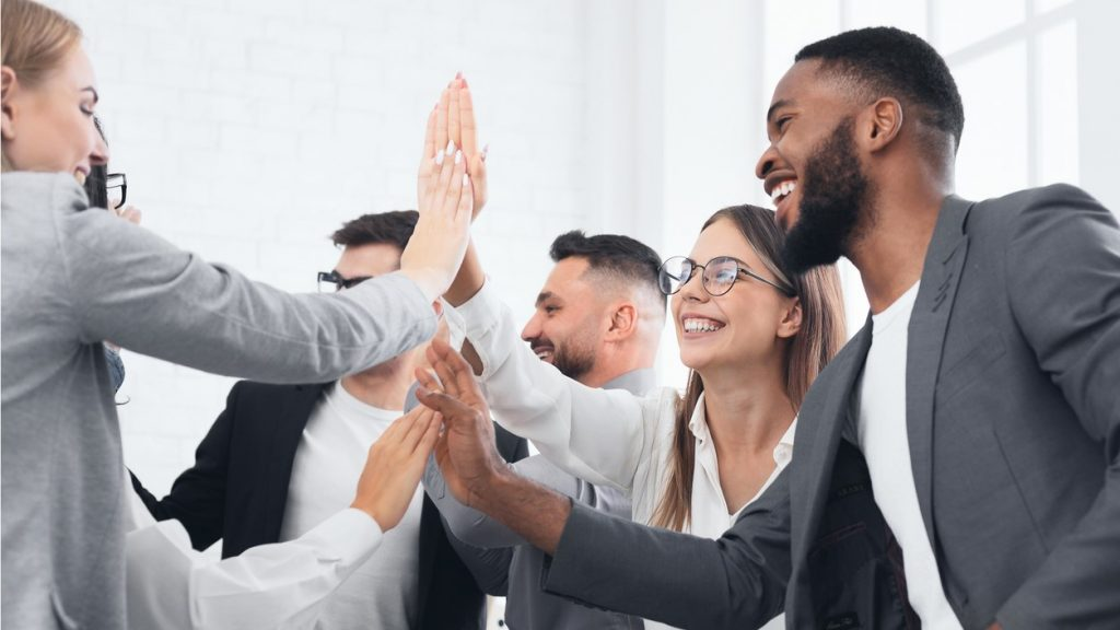 Team achievement, diverse business people giving high five at meeting. concept: most profitable businesses