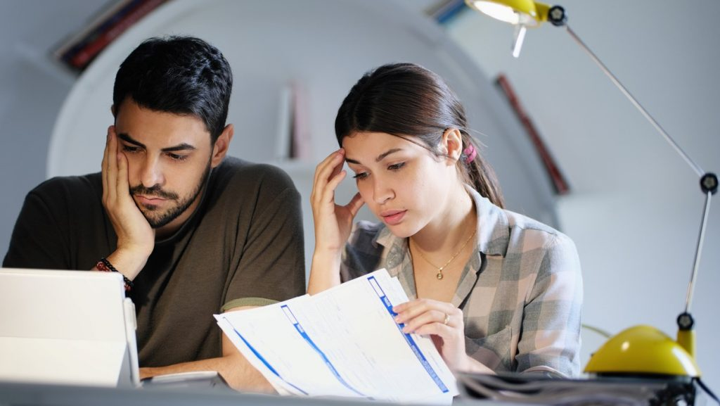 Young couple reviewing invoices and doing family business plan. Concept of money and economic problem for man and woman living together. concept: credit score harmful habits