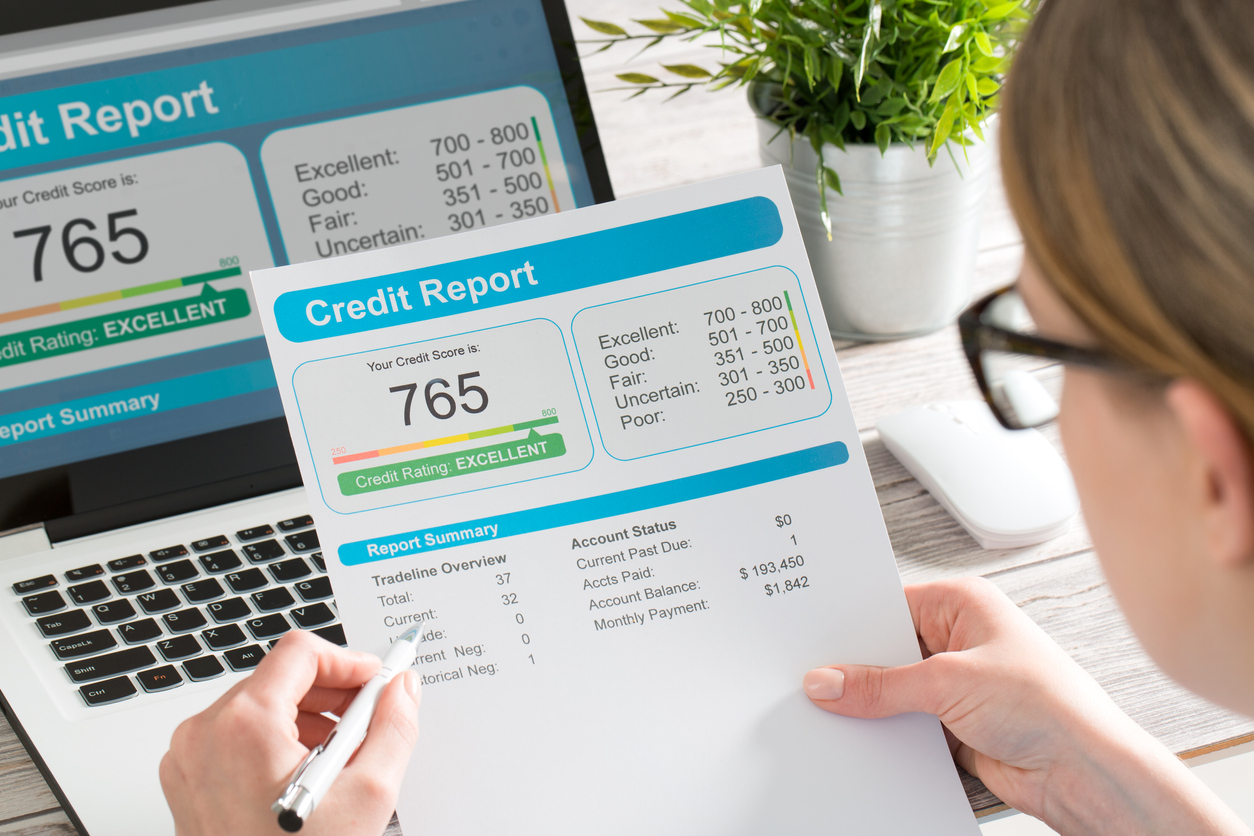 Woman checking her credit report on a paper copy and on computer screen. Concept:How to improve your credit score