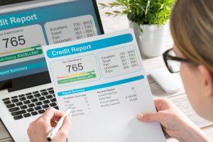 Mujer leyendo reporte de crédito en copia de papel y en pantalla de computadora. Concepto: Cómo aumentar tu puntaje de crédito