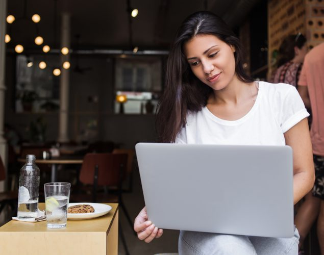 "Hispanic woman at café with laptop taking a business online course, representing ""cursos de negocios en línea"""