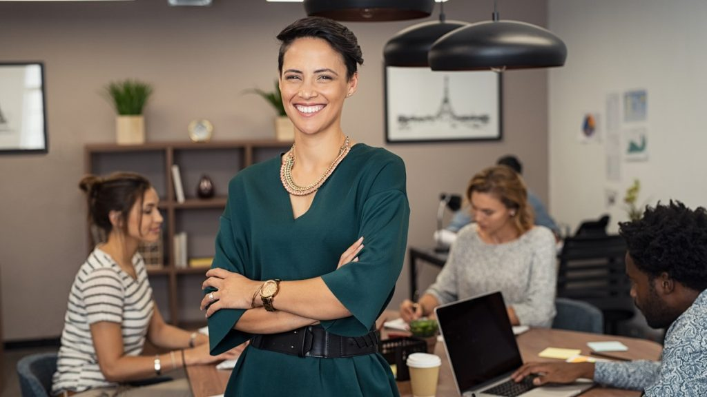 Portrait of successful business woman standing with her colleagues working in background at office. Portrait of cheerful fashion girl in green dress standing with folded arms and looking at camera. Beautiful businesswoman feeling proud and smiling. concept: credit for small business