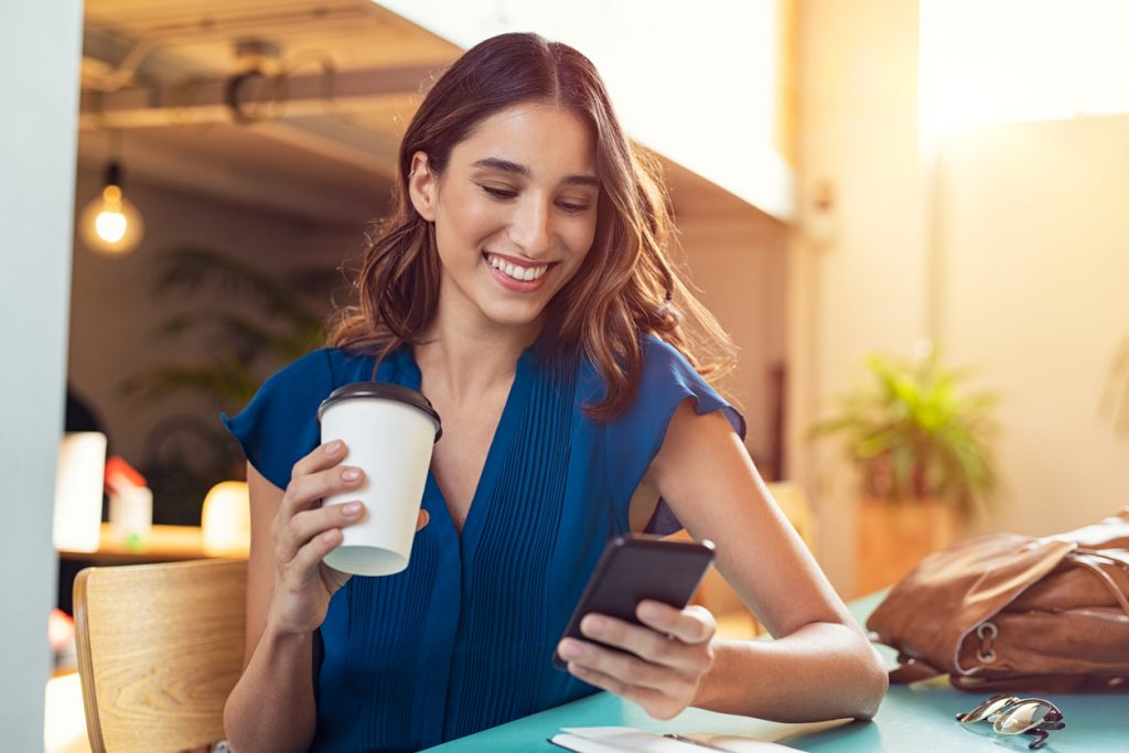 Young beautiful woman holding coffee paper cup and looking at smartphone while sitting at cafeteria. Happy university student using mobile phone. Businesswoman in casual clothes drinking coffee, smiling and using smartphone indoor. concept: snapchat