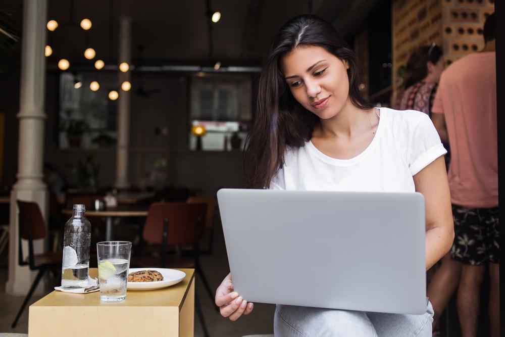 Mujer joven con laptop en cafetería tomando uno de los cursos de negocios en línea