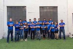 Equipo de Camino Financial con Sean y Kenny Salas al frente, visitiendo camisetas de la empresa: ejemplo de cómo crear una marca