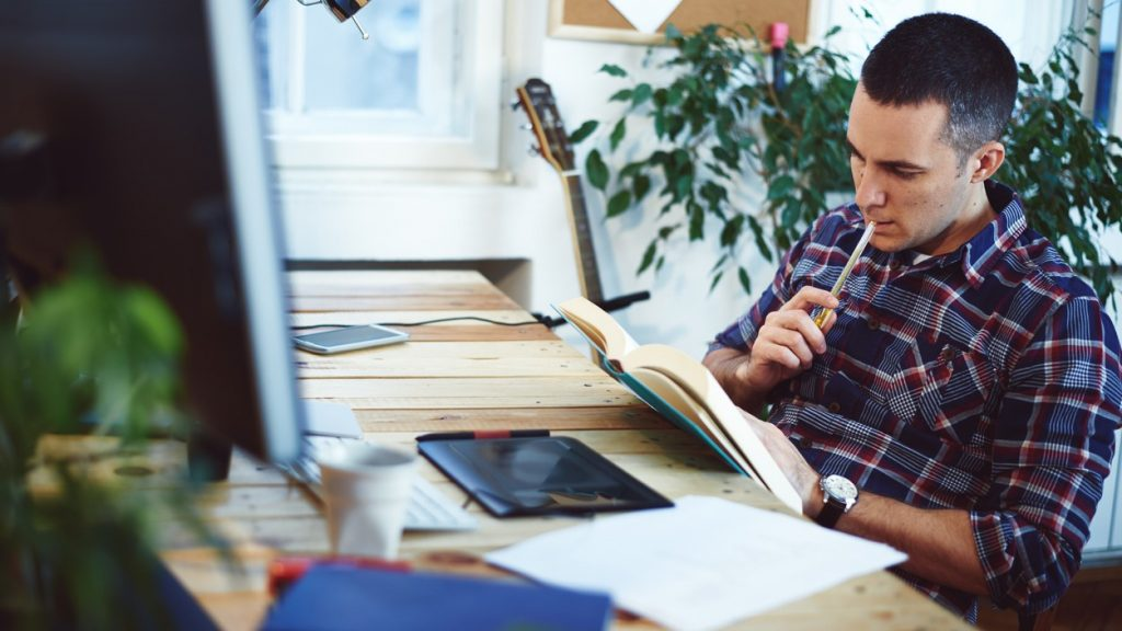Young man sitting in a home office, reading some book. concept: dba