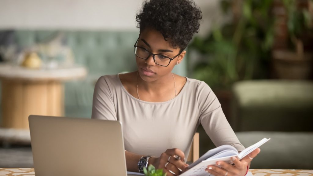 Focused young african american businesswoman or student looking at laptop holding book learning, serious black woman working or studying with computer doing research or preparing for exam online. concept: dba