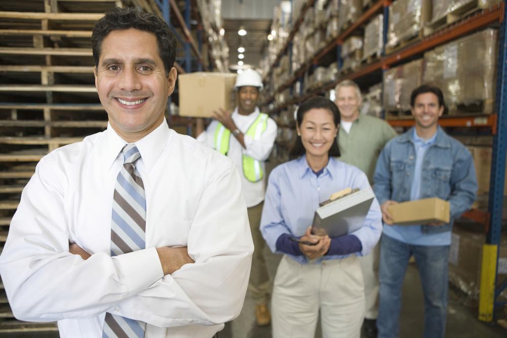 """Dueño de empresa latina con su equipo en un almacén, representando la idea de """"generar riqueza"""""""