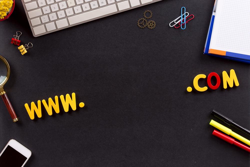 """Letras """"www.com"""" sobre escritorio con computadora y celular, para ilustrar la idea de """"construye un sitio web para tu empresa"""""""