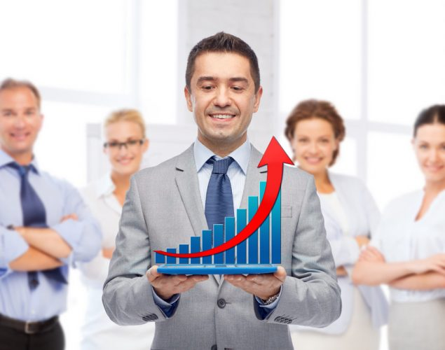Hispanic sales team with member holding a sales graphic