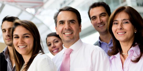 """Equipo de 6 empleados hispanos felices para ilustrar la idea de """"invertir en recursos humanos"""""""