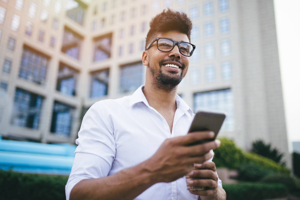 Hombre joven usando teléfono móvil para expresar la idea de oficina virtual