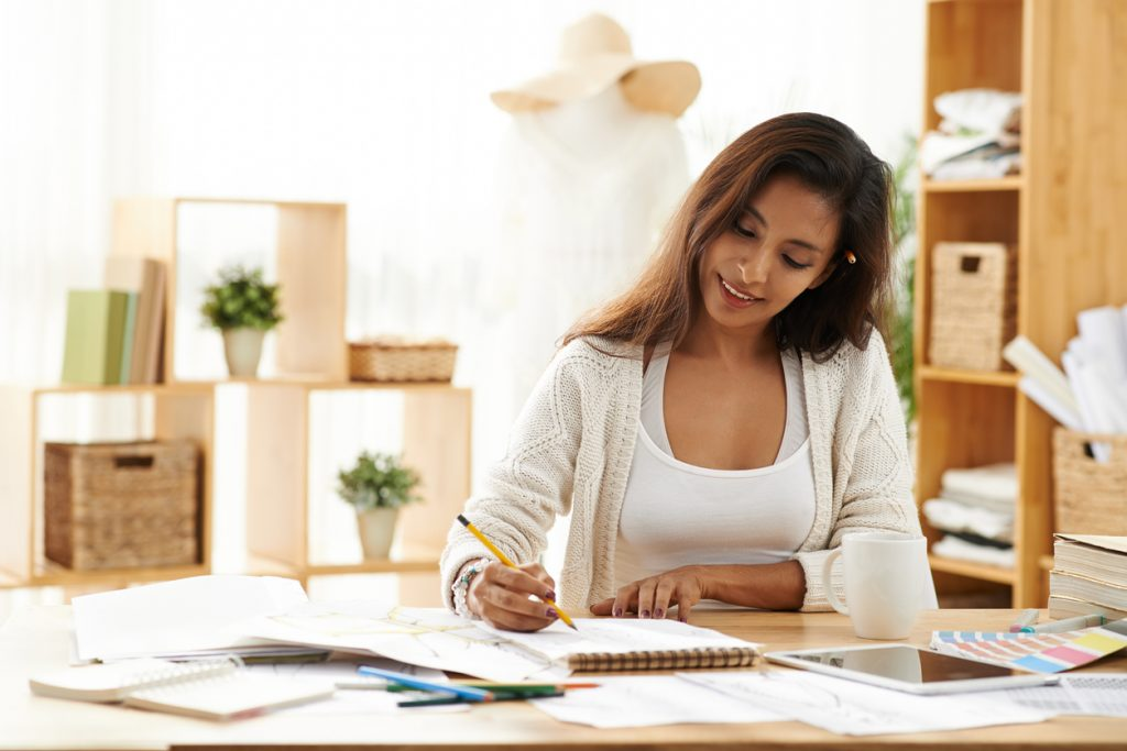 Portrait of smiling pretty woman enjoying her work in design studio. concept: small business loans for women