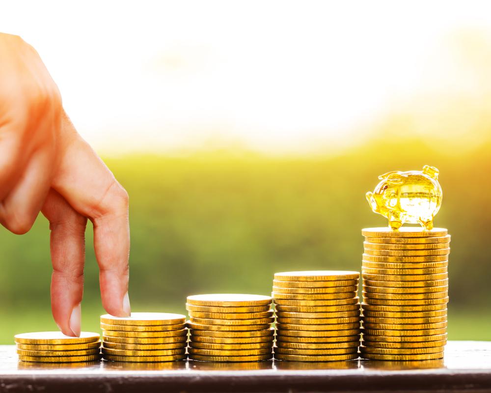 """Dedos escalando montoncitos de monedas para ilustrar la idea de """"pasos para obtener un crédito comercial"""""""