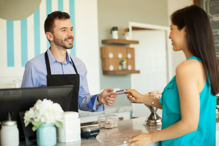 """Female customer paying business owner at the cash registry, to illustrate the idea of """"working capital"""""""