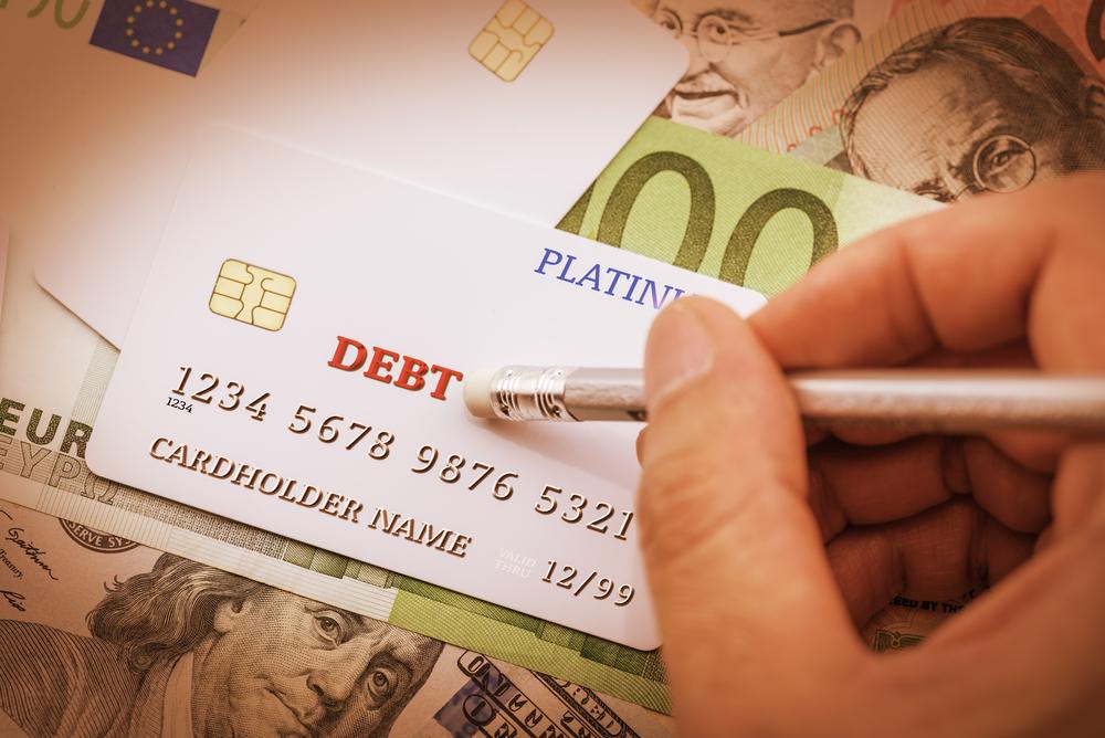"""Mano escribiendo """"debt"""" (deuda) sobre una tarjeta de crédito, para expresar la preferencia de los préstamos comerciales a corto plazo sobre las tarjetas de crédito"""