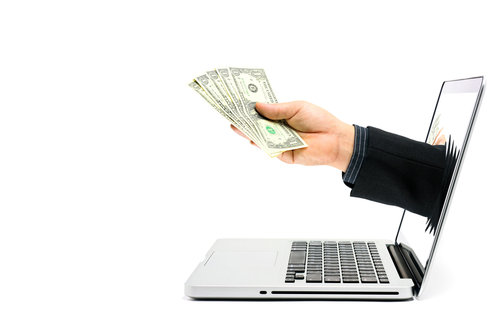 "Hand holding handful of dollars coming out of a laptop screen, to illustrate ""easy business loans"""