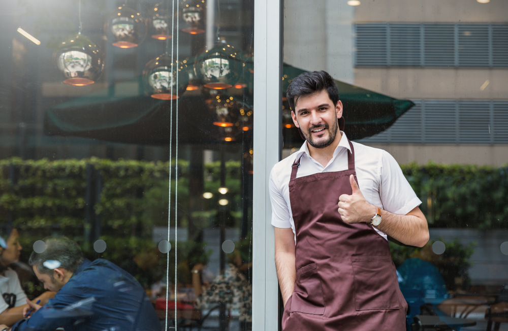 "Latino small business owner in front of his restaurant giving thumbs up to illustrate the idea ""build your business"""