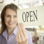 """Store Owner Turning Open Sign In Shop Doorway to illustrate the idea of """"business licenses"""""""