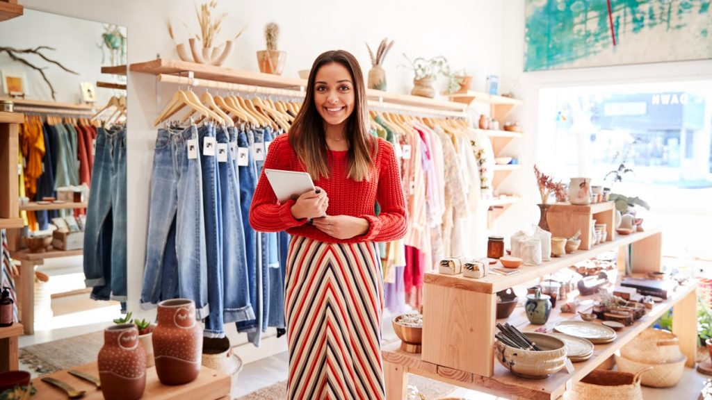 Portrait Of Female Owner Of Independent Clothing And Gift Store With Digital Tablet. concept: free cash flow