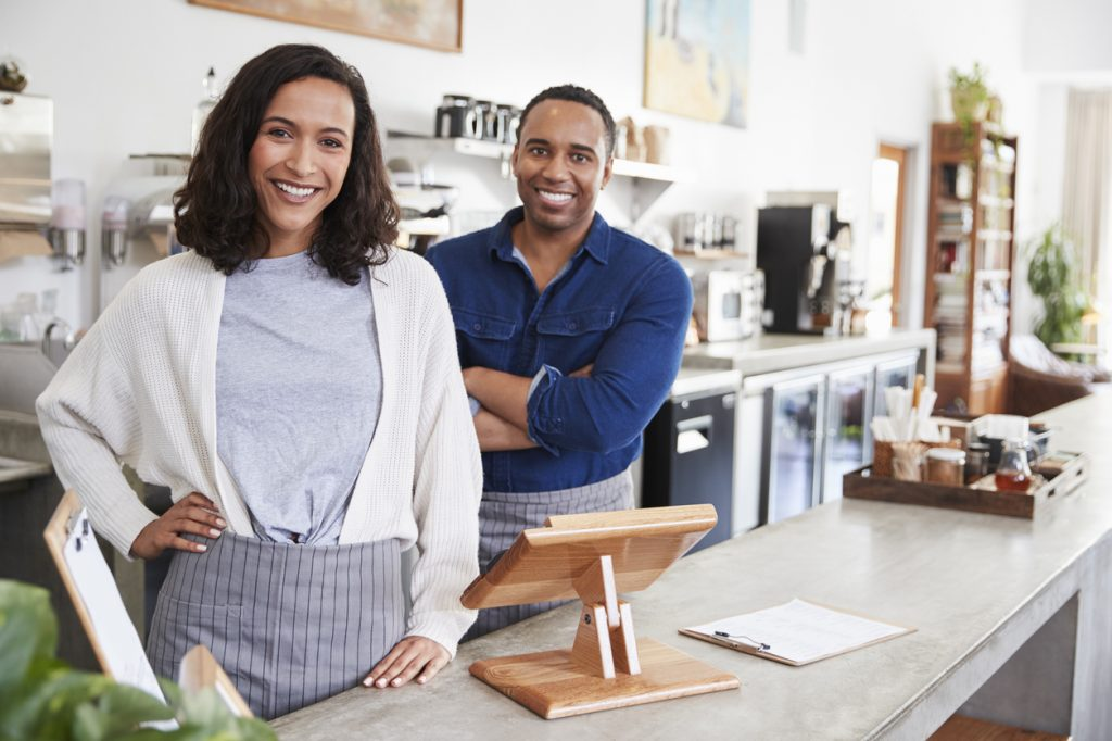 Mixed race couple behind the counter at their coffee shop to illustrate the idea of minority business loans