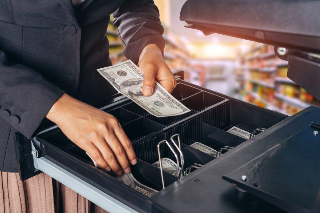 Mano de mujer depositando billetes en caja registradora. Concepto: Cómo calcular el flujo de caja libre de tu empresa - Fórmula de flujo de caja libre