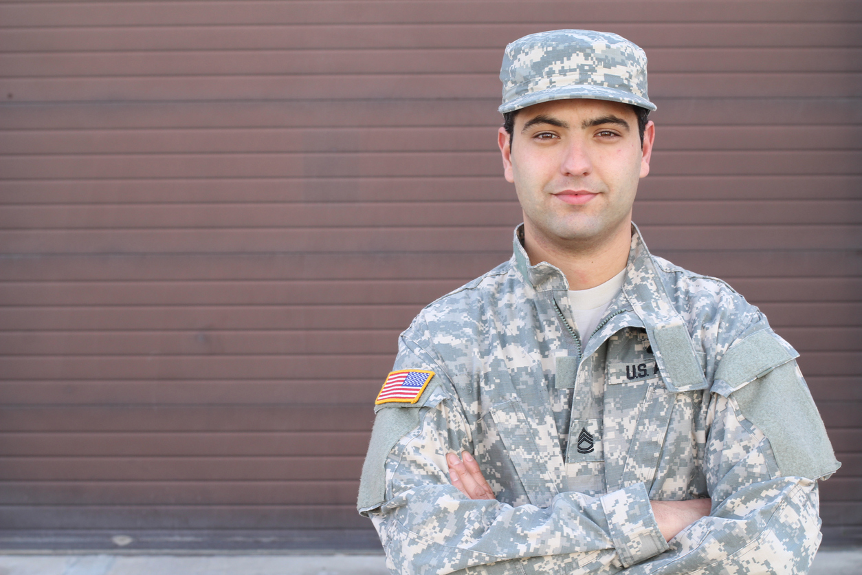 """Soldier smiling close up isolated with copy space to illustrate the idea of """"business loans for veterans""""."""