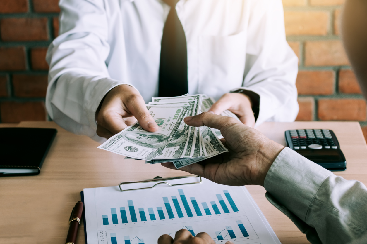 Lender giving dollar bills to borrower over desk office