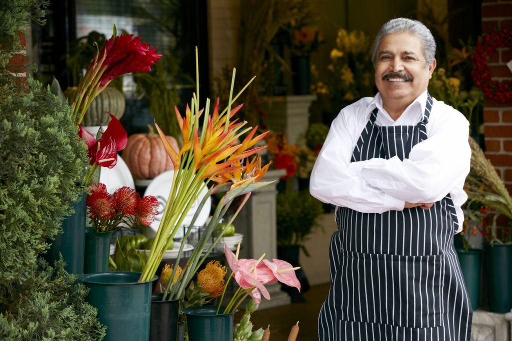 "Male Hispanic Florist Outside Shop Smiling To Camera, to illustrate ""ITIN loans""."