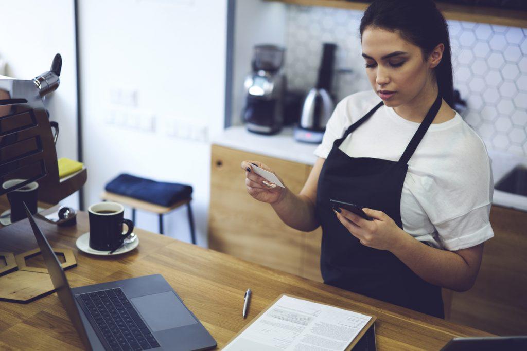 Dueña de negocios hispanan al mostrador en su negocio realizando un pago por teléfono con tarjeta de crédito para ilustrar la idea: préstamos comerciales no garantizados y tarjetas de crédito.