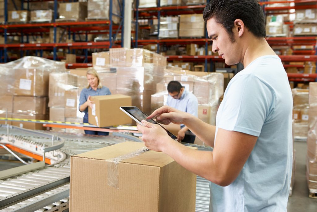 Worker Using Tablet Computer In Distribution Warehouse Looking At Notes