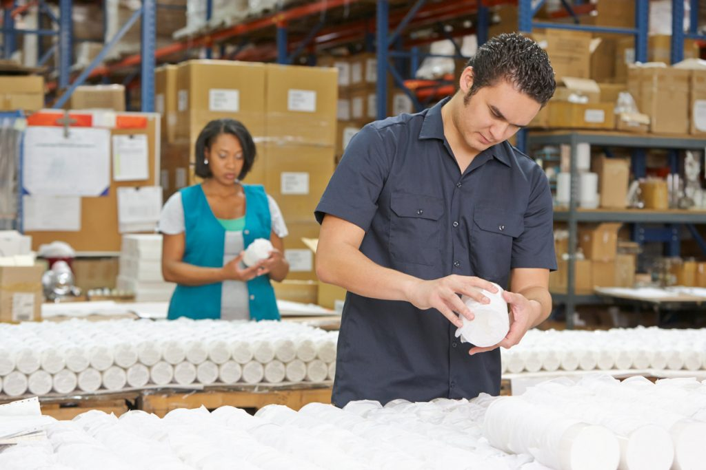 """Hispanic Male Factory Worker Checking Goods On Production Line, to ilustrate the idea """"Porduction costs"""""""