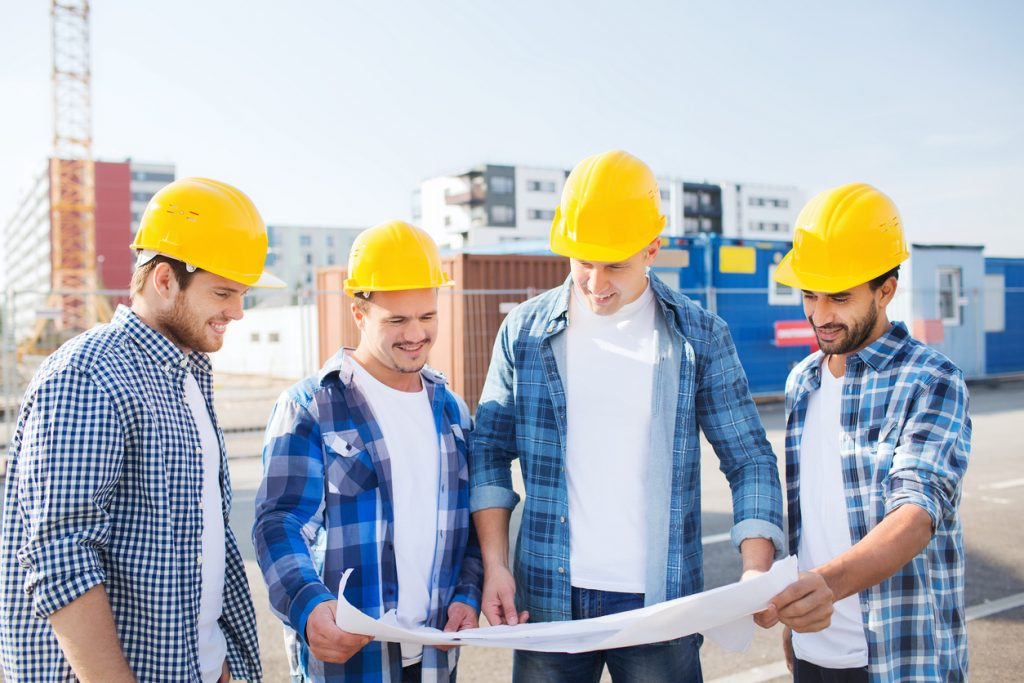"Group of four contractors in construction site gathering around a blueprint to illustrate the idea ""how to become a contractor"""