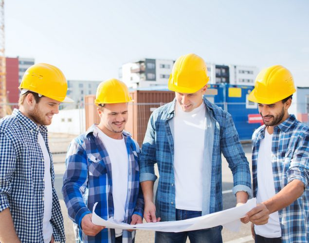 """Group of four contractors in construction site gathering around a blueprint to illustrate the idea """"how to become a contractor"""""""